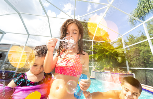 Fototapeta Children playing outdoors in a swimming pool blowing bubbles obraz