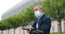 Senior Gray-haired Man In Medical Mask Standing At Bike On Street And Disinfecting Hands With Spray Sanitizer. Old Grandfather Spraying Disinfectionand Cleaning Skin From Germs Outdoors. Disinfector.