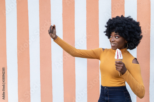 Funny African American woman with curly hairstyle, taking self-portrait on smartphone with ice cream in waffle cone of strawberry flavor, posing on striped background, side view Wallpaper Mural