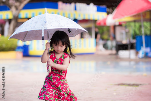Adorable little girl wearing a red dress with watermelon prints walks an umbrella on a drizzly day in the rainy season Canvas Print