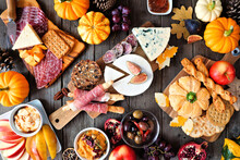 Autumn Theme Charcuterie Table Scene Against A Dark Wood Background. Variety Of Cheese And Meat Appetizers. Overhead View.