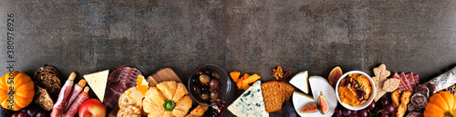 Fall charcuterie border against a dark stone banner background. Assorted cheese and meat appetizers. Copy space.