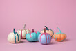 Autumn layout made of colorful pumpkins with dripping paint on pink background. Minimal Fall or Halloween concept.