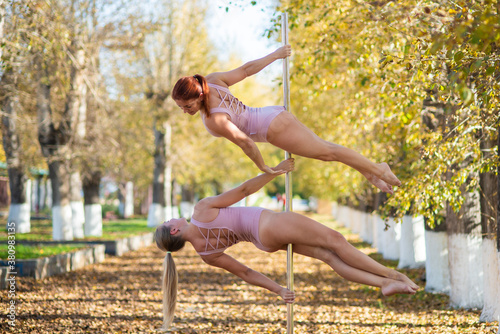Tela Two beautiful gymnasts do pair tricks on a portable platform in a beautiful autumn park