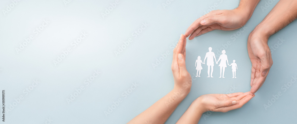 Fototapeta Family care concept. Hands with paper silhouette on table.