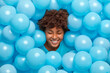 Overjoyed dark skinned woman laughs happily sticks out head through blue balloons happy to celebrate hens party smiles broadly and shows white teeth. Afro American girl prepares for anniversary