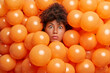 Leinwandbild Motiv Surprised birthday girl poses over inflated orange party balloons stares bugged eyes expresses great wonder or surprise. Young Afro American woman enjoys anniversary event has shocked expression