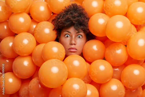 Fototapeta Surprised birthday girl poses over inflated orange party balloons stares bugged eyes expresses great wonder or surprise. Young Afro American woman enjoys anniversary event has shocked expression obraz