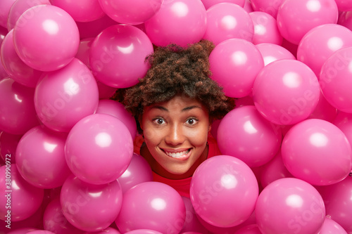 Fototapeta Attractive curly haired woman poses among pink balloons during festive day happy to receive congrats and looks happily at camera. Holiday event concept. Pretty girl being on party for teenagers obraz