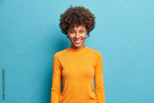 Half length shot of pretty cheerful young Afro American woman with nice beaming smile pleased expression dressed in casual orange jumper isolated on blue background Fototapet