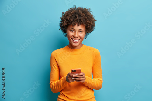 Fototapeta Photo of cheerful dark skinned young woman holds modern device in hands browses her favorite web page surfs social media sends sms smiles positively dressed casually isolated on blue background obraz
