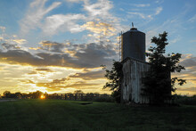 Sunrise And Grain Silo At A Farm