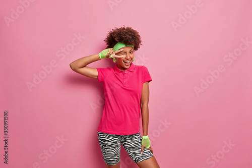 Photo Playful happy dark skinned woman winks eye and gestures v sign has crazy mood chills indoor poses in casual clothes against pink background