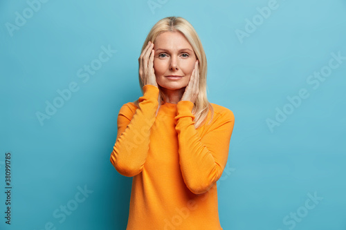 Beauty aging and cosmetology concept. Good looking serious woman with blonde hair touches face gently has healthy skin after applying anti aging cream wears bright sweater isolated on blue wall