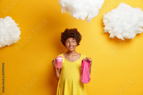 Fototapeta Pensive pregnant young Afro American woman dreams about child and future life holds feeding bottle and baby clothes bites lips looks thoughtfully away poses against yellow background with clouds obraz