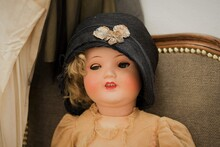 An Antique Victorian Doll In Detail With A Hat Sitting On The Sofa