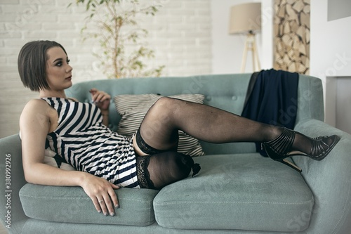 Fényképezés young amputee woman in stockings and shoes lies on the couch