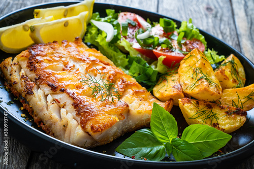 Fish dish - fried cod fillet with potatoes and vegetable salad on wooden table