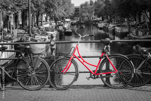 Fototapety, obrazy: A picture of a red bike on the bridge over the channel in Amsterdam. The background is black and white.