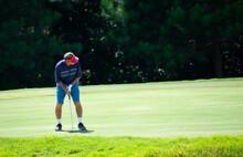 A Man Golfer Putting A Golf Ba...
