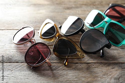 Many different stylish sunglasses on wooden background Tableau sur Toile