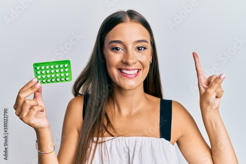 Vászonkép Young hispanic woman holding birth control pills smiling with an idea or questio