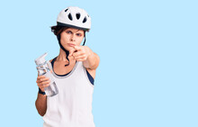 Beautiful Young Woman With Short Hair Wearing Bike Helmet And Holding Water Bottle Pointing With Finger To The Camera And To You, Confident Gesture Looking Serious