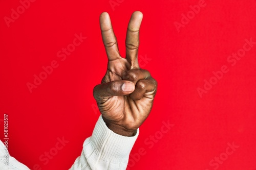 Fototapeta Arm and hand of african american black young man over red isolated background counting number 2 showing two fingers, gesturing victory and winner symbol obraz
