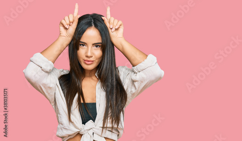 Fotografía Young beautiful hispanic girl wearing casual clothes doing funny gesture with fi