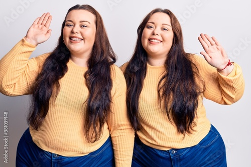Fototapeta Young plus size twins wearing casual clothes waiving saying hello happy and smil