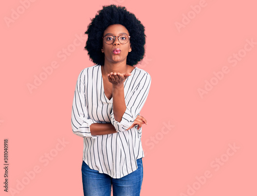 Obraz na plátně Young african american woman wearing casual clothes and glasses looking at the camera blowing a kiss with hand on air being lovely and sexy