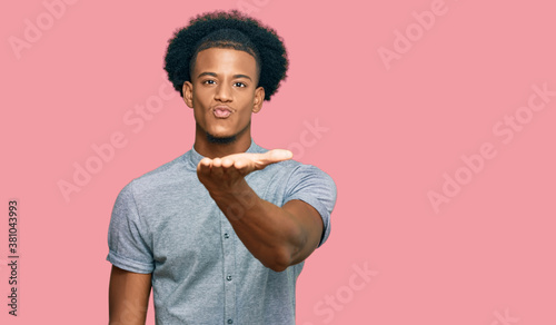 Fotografie, Obraz African american man with afro hair wearing casual clothes looking at the camera blowing a kiss with hand on air being lovely and sexy