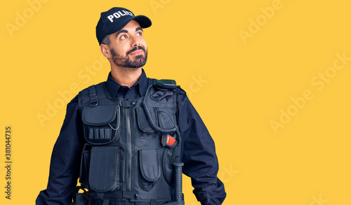 Canvas Young hispanic man wearing police uniform smiling looking to the side and staring away thinking
