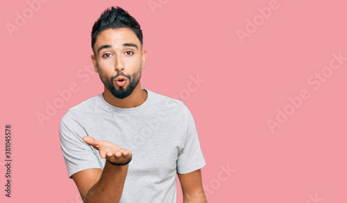 Fotografie, Obraz Young man with beard wearing casual grey tshirt looking at the camera blowing a kiss with hand on air being lovely and sexy