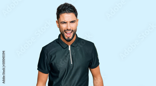 Young man with beard wearing sportswear winking looking at the camera with sexy expression, cheerful and happy face Wallpaper Mural