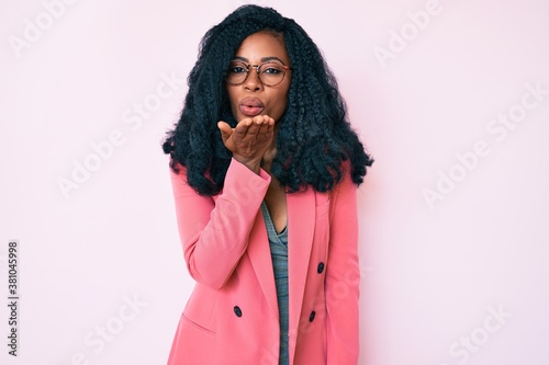 Fototapeta Beautiful african woman wearing business jacket and glasses looking at the camera blowing a kiss with hand on air being lovely and sexy