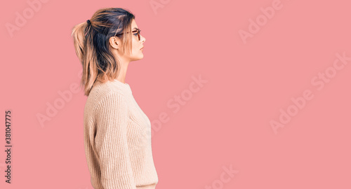 Fototapeta Young beautiful woman wearing casual winter sweater and glasses looking to side, relax profile pose with natural face with confident smile. obraz