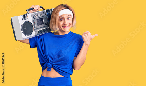 Photo Young blonde woman wearing sportswear holding boombox, listening to music pointi