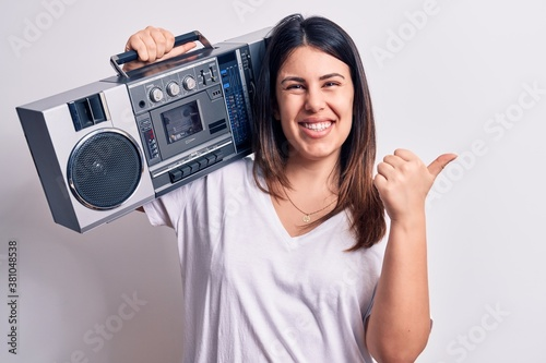 Young beautiful woman listening to music using vintage boombox over white backgr Wallpaper Mural