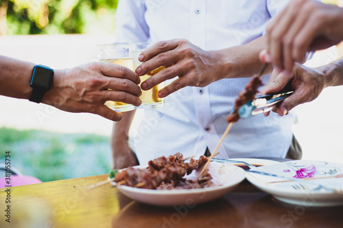 Fototapeta Young man holding a beer glass and drinking with his friends at an outdoor party at home. obraz