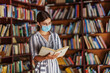 Young attractive female student in dress with brown hair standing in the library with mask on face and reading a book. Studying during corona virus pandemic.