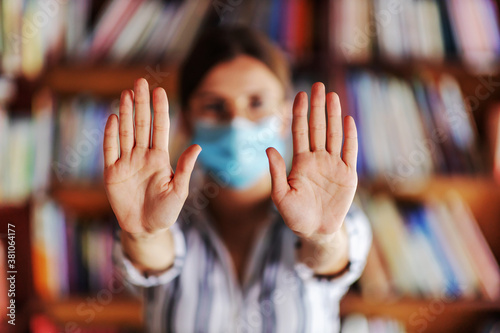Slika na platnu Young college girl with face mask on standing in library and showing clean hands