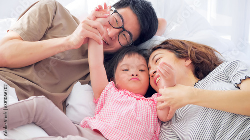 Fotografiet Happy family with mother, father and disabled daughter spending time together at home