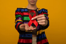 Woman Holds Red Ribbon To Awar...