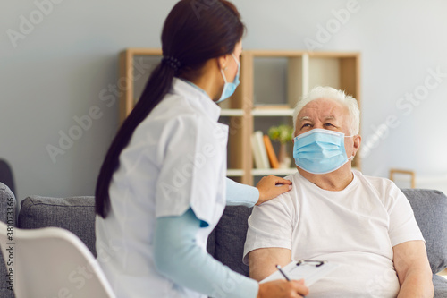 Caring supportive doctor visiting senior male patient at home during coronavirus Fototapete