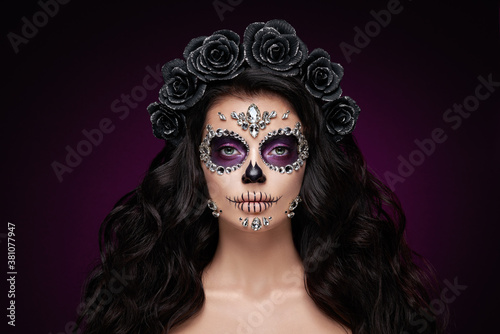 Fototapeta Portrait of a woman with sugar skull makeup over red background