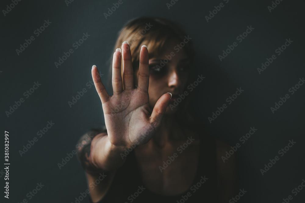 Fototapeta Stop violence against women! Woman raised her hand for dissuade standing against dark wall.