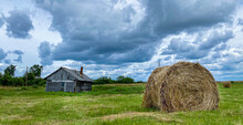 Rural Landscape With Harvesting Field, Hayroll And Small Old House