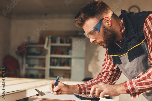 Young man calculates and writes it down on paper in a home workshop Wallpaper Mural
