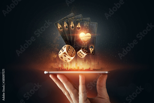 Fotografia Creative background, online casino, in a man's hand a smartphone with playing cards, roulette and chips, black-gold background